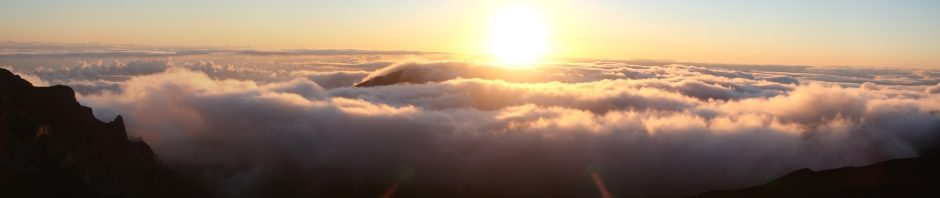 The sun rises from the clouds over Maui, taken from the peak of Haleakala